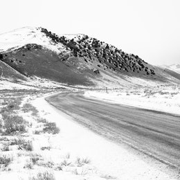A snowy road in the National Elk Refuge, leading towards Millers Butte.