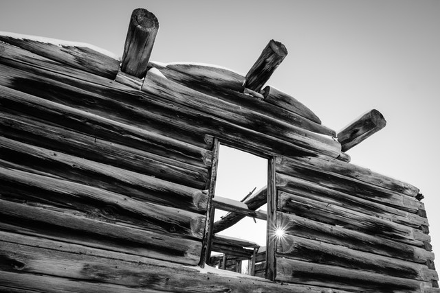The facade and window of the Shane Cabin at Grand Teton National Park, with the sun shining between the logs.