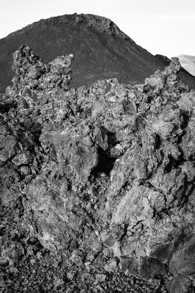 A close-up view of jagged, spiky ʻaʻa  lava. In the background, a spatter cone.