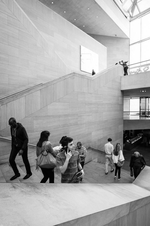 People walking up the stairs at the East Building of the National Gallery of Art in DC.