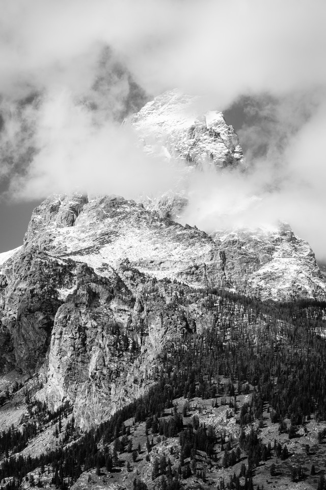 Grand Teton and Disappointment Peak. The summit of the Grand is covered in snow, and partially hidden by clouds.