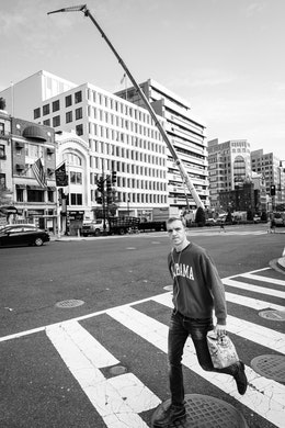 A man crossing the street in front of an enormous crane on Connecticut Avenue NW.