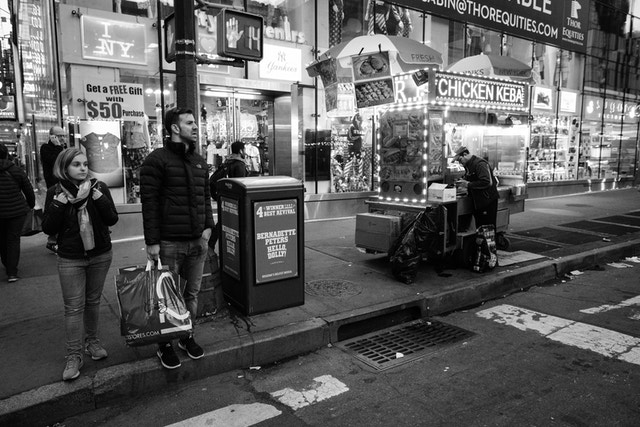 People waiting to cross Eighth Avenue next to a fast food cart.