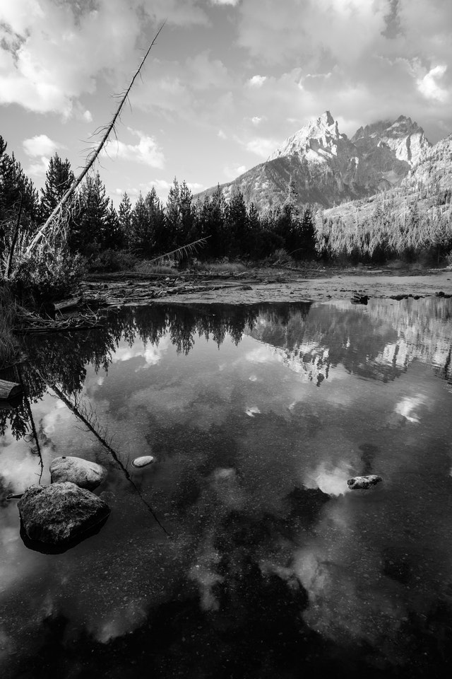 Teewinot Mountain, Grand Teton, and Mount Owen, seen from the outlet of String Lake. Rocks and the reflection of the clouds can be seen in the water.