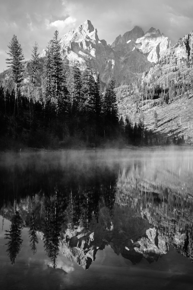 Teewinot Mountain, Grand Teton, and Mount Owen, reflected off the mist-covered surface of String Lake.