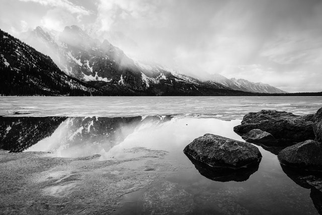 A spring storm clearing over a half-frozen Jenny Lake. In the foreground, boulders on the shore of Jenny Lake; in the background, clouds moving past Storm Point, Symmetry Spire, and Mount Saint John.