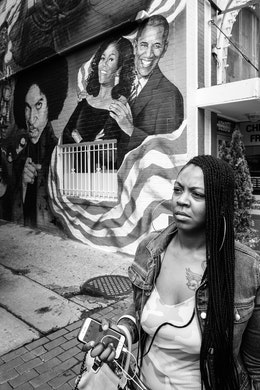 A woman walking past a mural of President Obama, Michelle Obama, and Prince, on U street.