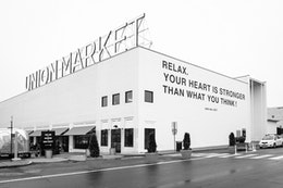 """The facade of Union Market, featuring a mural with a quote from Yoko Ono that reads """"Relax, your heart is stronger than what you think""""."""