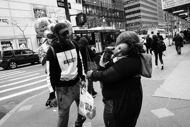 A child looking at the camera while being carried by their parents on Fifth Avenue.