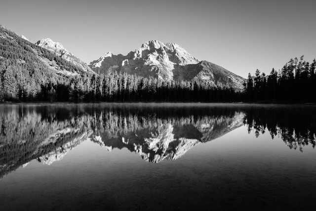 Mount Moran, reflected in the misty waters of String Lake, shortly after dawn.