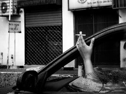 A woman smokes in her car on a rainy day at the Luis Roche Ave. in Caracas.