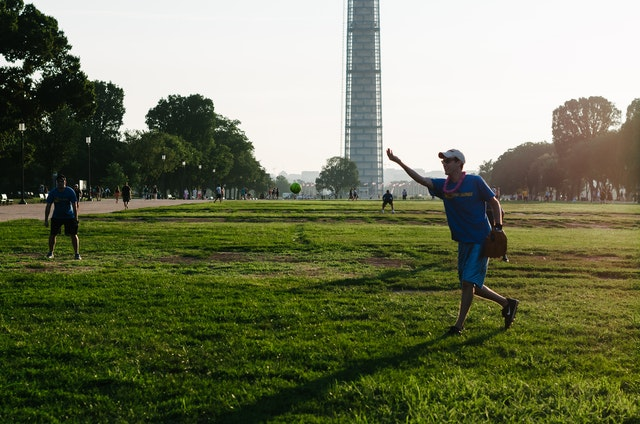 A man playing softball on the National Mall at sunset.