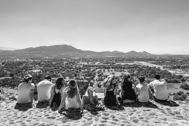 A group of tourists sitting at the edge of the Pyramid of the Sun in Teotihuacán.