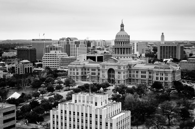 Black and white view of the Texas State Capitol from a nearby rooftop.