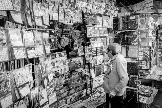 An old woman shopping at a newsstand in the historic center of Mexico City.