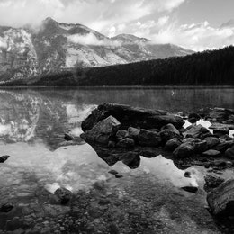 Rocks at the shore of Phelps Lake, with Albright Peak and Death Canyon reflected in the water.
