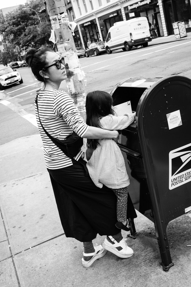 A woman lifting a child so she can drop a letter in a mailbox on Grand Street, Williamsburg.