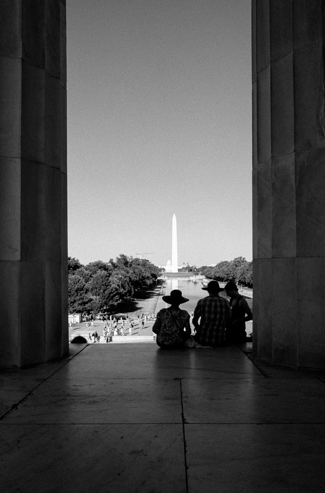 Tourists looking at the Reflecting Pool and the Washington Monument from the Lincoln Memorial.