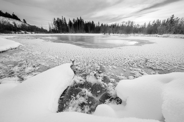The frozen surface of a pond, covered in snow & ice crystals.