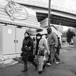 A group of people walking towards the Maine Avenue Fish Market in Washington, DC.