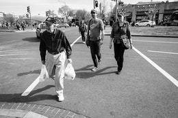 A smiling older man carrying grocery bags crossing Pennsylvania Avenue SE near Eastern Market.