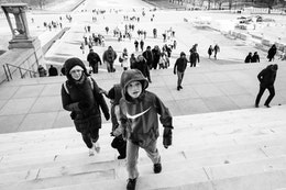 Two kids and a woman climbing the stairs of the Lincoln Memorial.