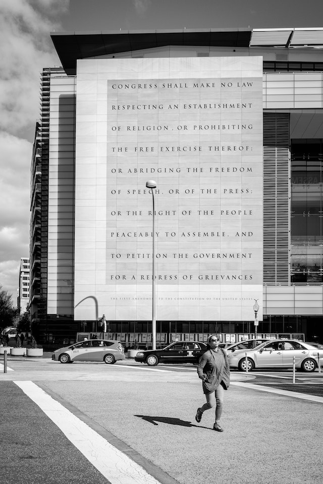 A pedestrian crossing Pennsylvania Avenue in front of the Newseum, which has the First Amendment engraved on its facade.