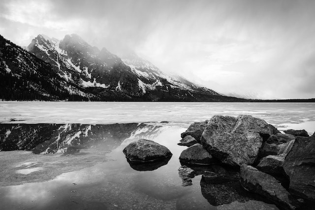 A spring storm moving over a half-frozen Jenny Lake. In the foreground, boulders on the shore of Jenny Lake; in the background, clouds moving over Storm Point, Symmetry Spire, and Mount Saint John.