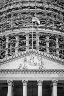 The pediment of the United States Capitol building on the West Front, with the dome covered in scaffolding.