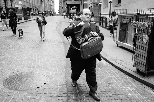 A man in a suit walking on Wall Street while trying to open his suitcase.