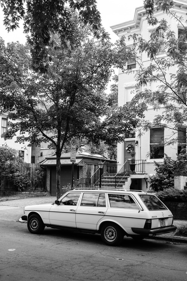 A Mercedes station wagon parked in front of a row house in Capitol Hill.