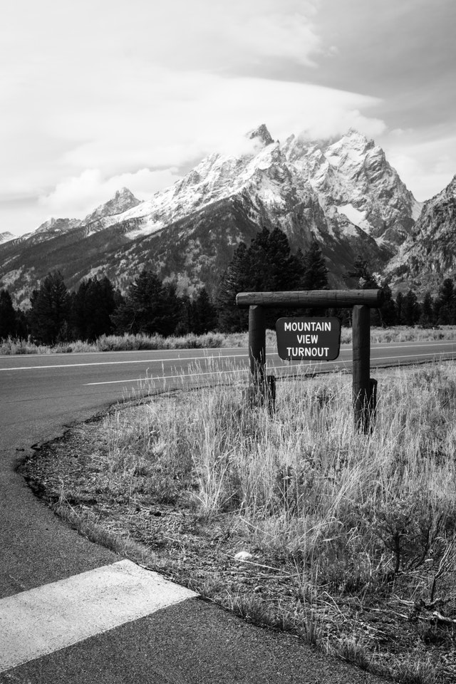 A sign at the Mountain View Turnout, with Teewinot Mountain and Mount Owen in the background.