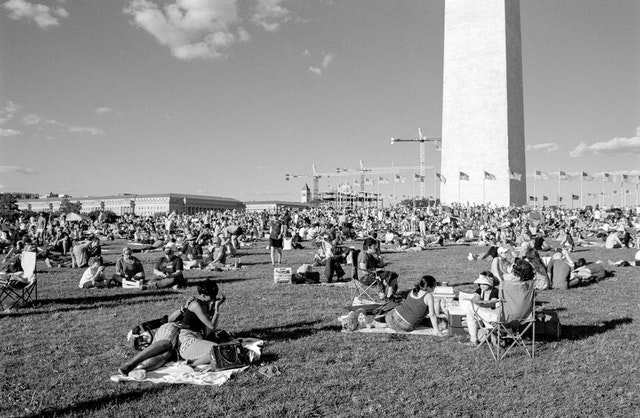 People sitting on the lawn in front of the Washington Monument.