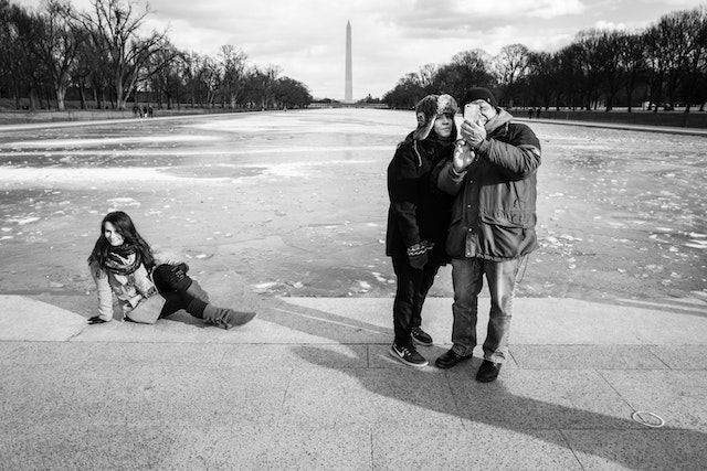 Two people taking a selfie in front of the Lincoln Memorial Reflecting Pool, while another person poses in the background.