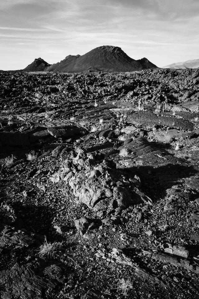 A field of pahoehoe and ʻaʻa lava in front of a couple of spatter cones.