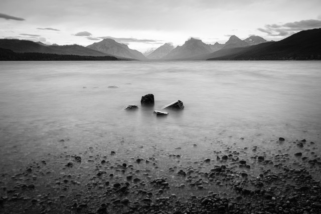 A long exposure photo of a group of four large rocks near the shore of Lake McDonalds during a storm, with the mountains in the background.