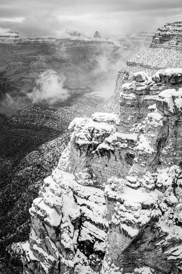 The walls of the South Rim covered in snow during a clearing snowstorm.
