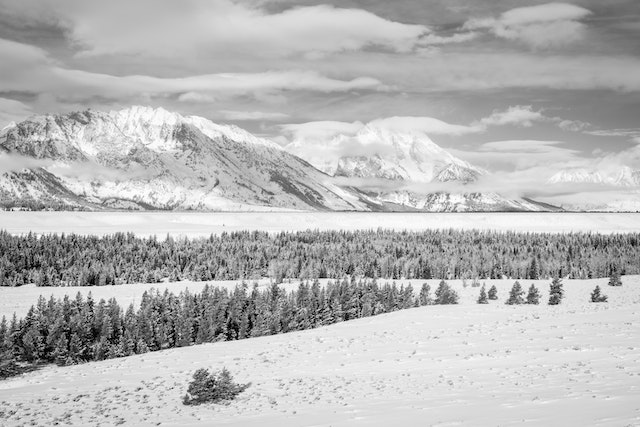 Rockchuck Peak and Mount Moran, partially hidden by clouds during winter, from Teton Point turnout.