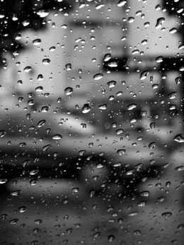 Raindrops on the windshield on the street.