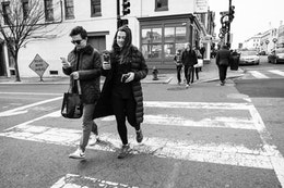 Two people crossing 31st street in Georgetown while looking at their phones.