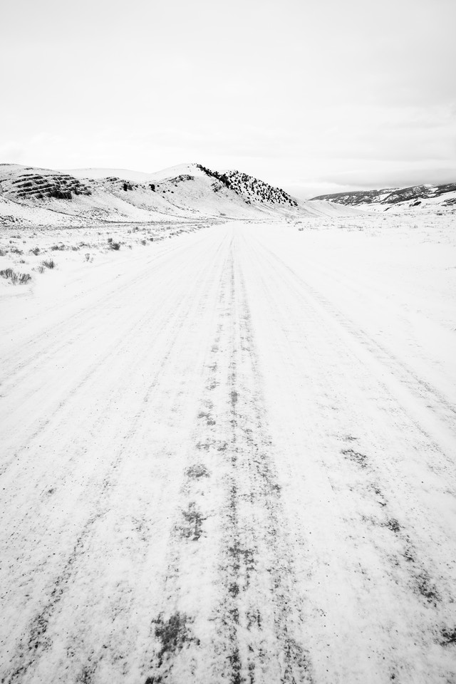 National Elk Refuge road covered in snow, with the north end of Millers Butte in the distance.