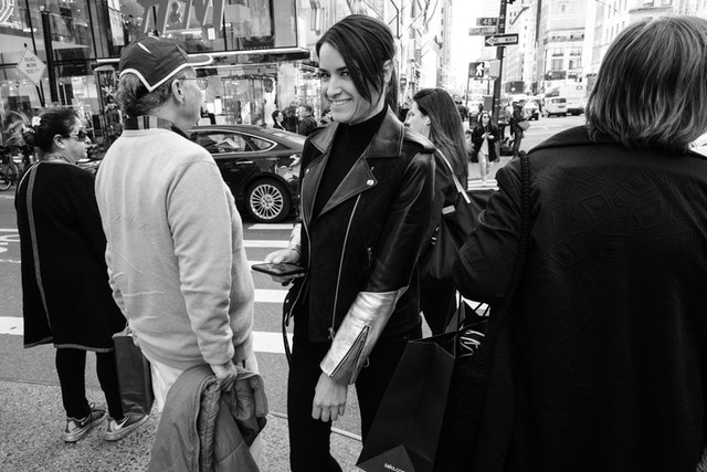 A person in a leather jacket smiling at the camera as they cross 48th Street in New York City.