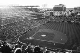 A Nationals vs. Orioles baseball game at Nationals Park at sunset, seen from the stands on the first base side.