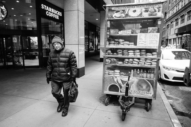 A man walking past a bagel & coffee cart in the Financial District.
