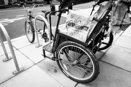 Close-up of an empty pedicab parked on the curb.
