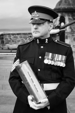 The District Gunner from the 105th Regiment Royal Artillery, holding a shell casing from the One O'Clock Gun.