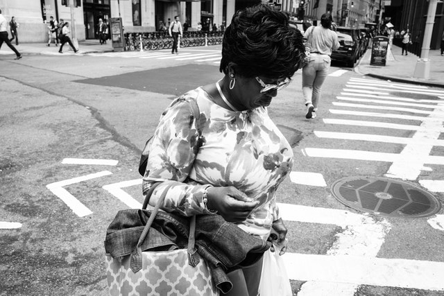 A woman wearing sunglasses crossing Broad Street in New York's Financial District.