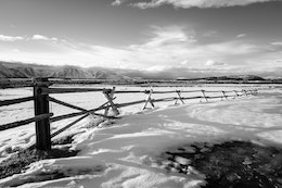 A wooden fence in the snow, with the Teton range seen in the background.