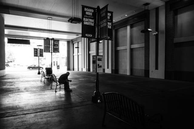 A man sitting on a bench at the electric shuttle station in Chattanooga.
