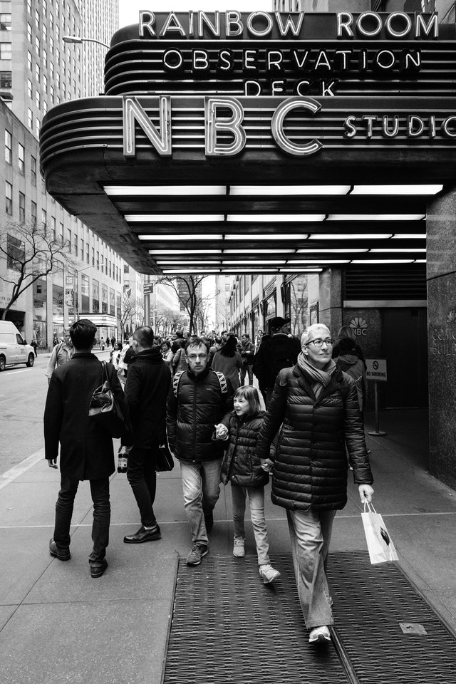 A family holding hands while walking by Rockefeller Center in New York City.